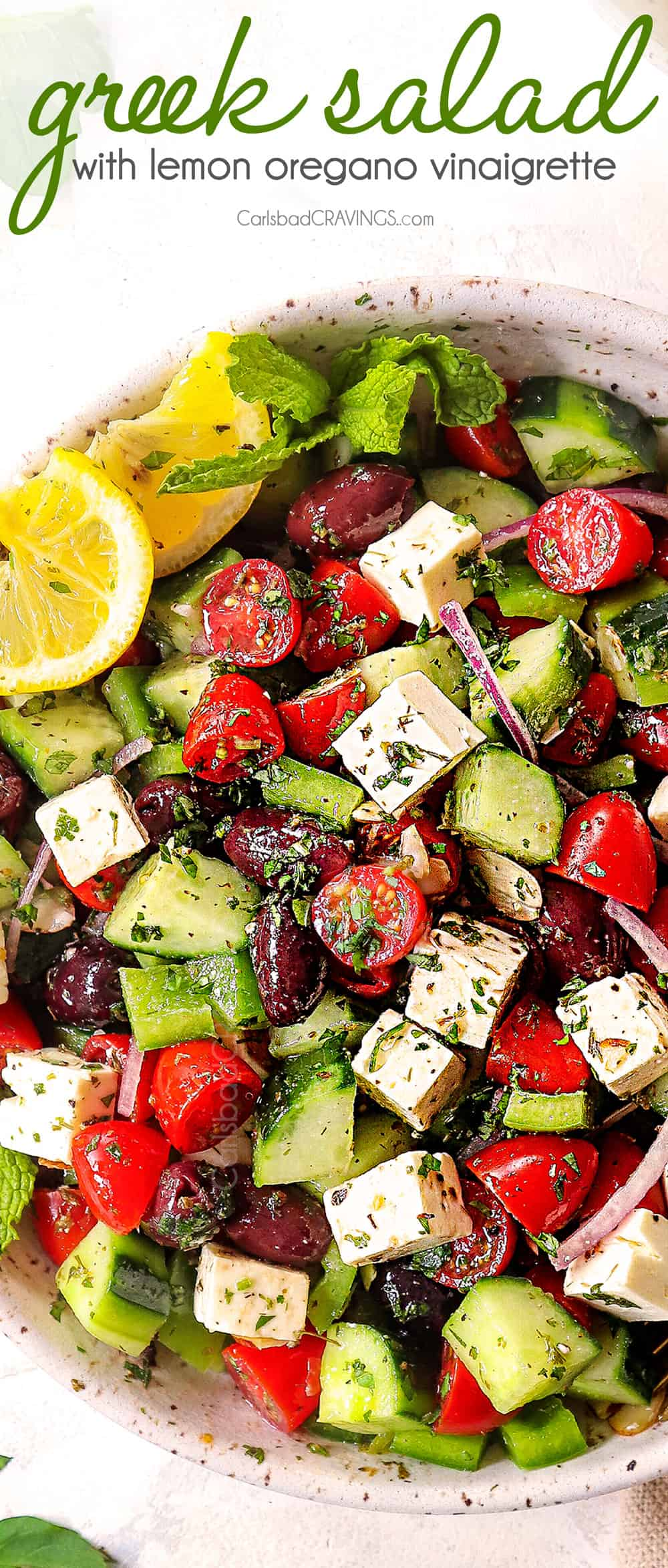 showing how to make Greek Salad recipe by mixing tomatoes, cucumbers, Kalamata olives, red onions and feta together