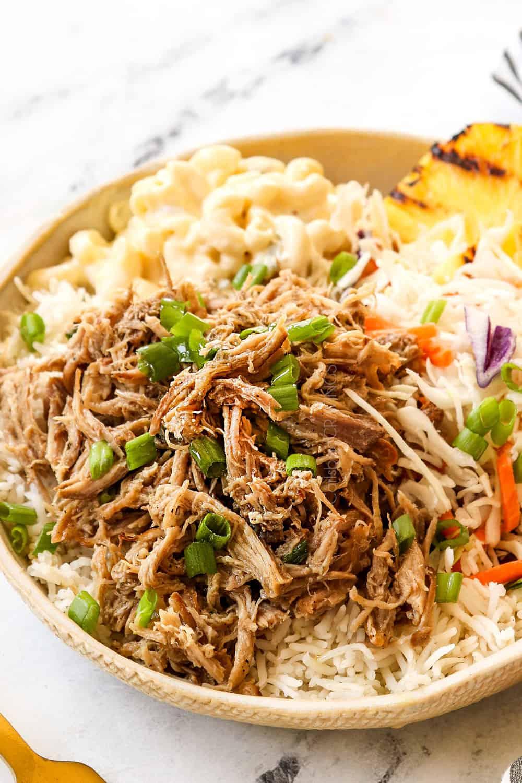 a plate of Kalua Pork recipe with rice, pineapple and macaroni salad
