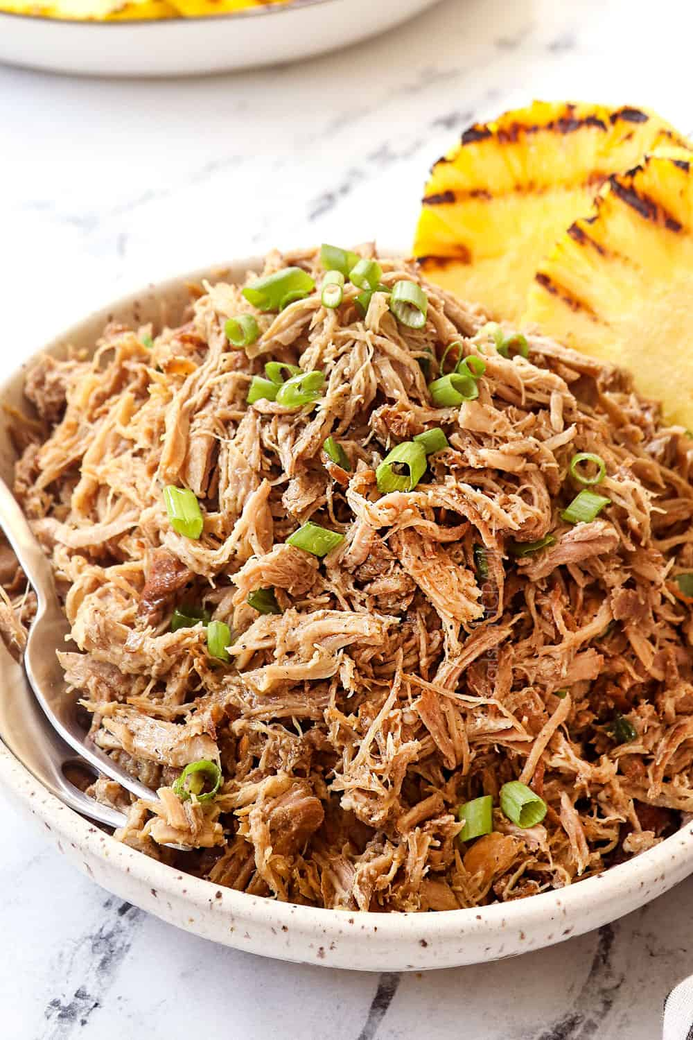 a bowl of Kalua pork recipe garnished with green onions