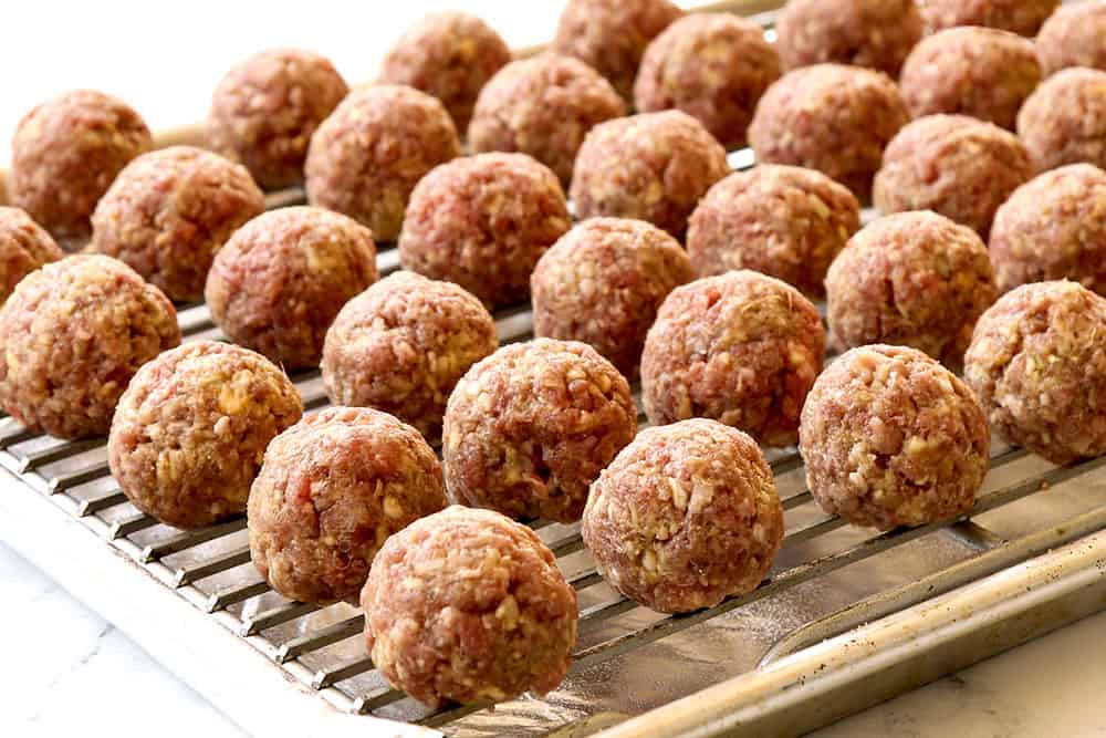 showing how to make teriyaki meatball recipe by placing rolled meatballs on a baking sheet with baking rack on top
