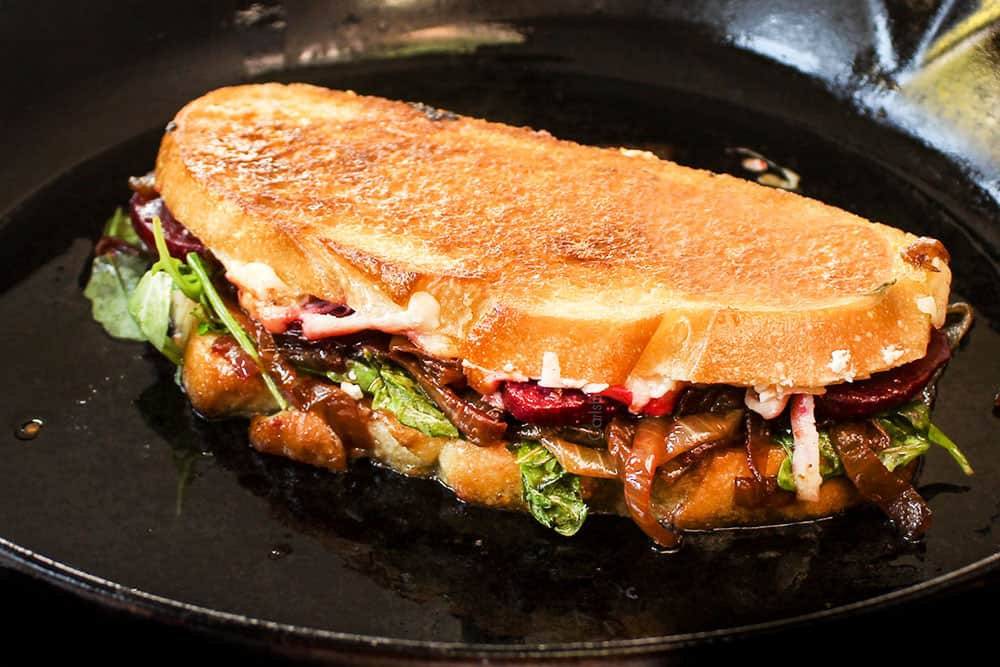 showing how to make gourmet grilled cheese by toasting in a cast iron skillet