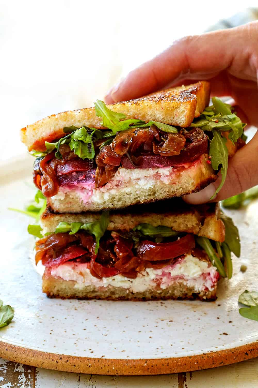 grilled cheese sandwich recipe stacked on top of each other with goat cheese, caramelized onions and arugula