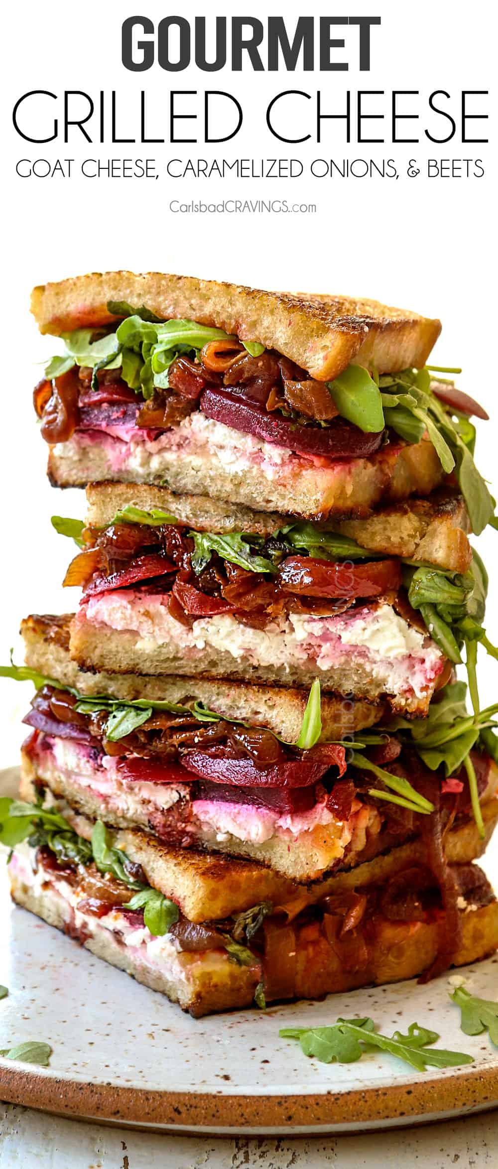 gourmet grilled cheese sliced and stacked with caramelized onions, goat cheese and arugula