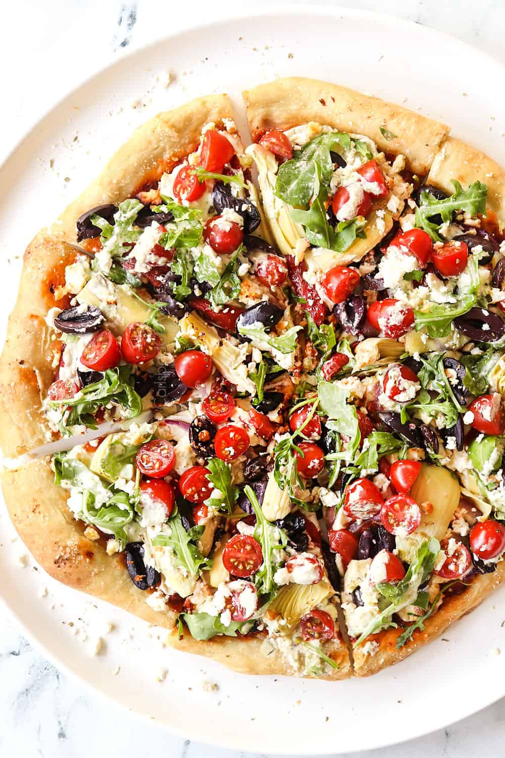 showing how to make Greek pizza recipe by adding arugula, tomatoes, cucumbers and tzatziki to the top of the baked pizza