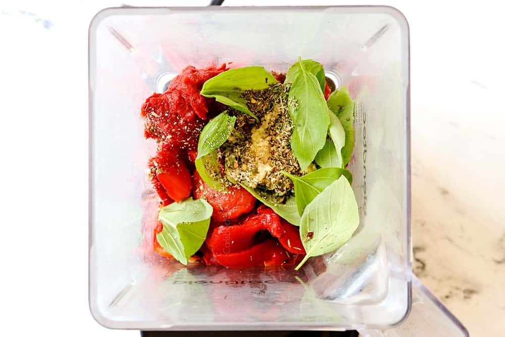 top view of showing how to make roasted red pepper sauce by adding roasted red peppers, garlic, basil, tomato paste, oregano, parsley, thyme and red pepper flakes to a blender