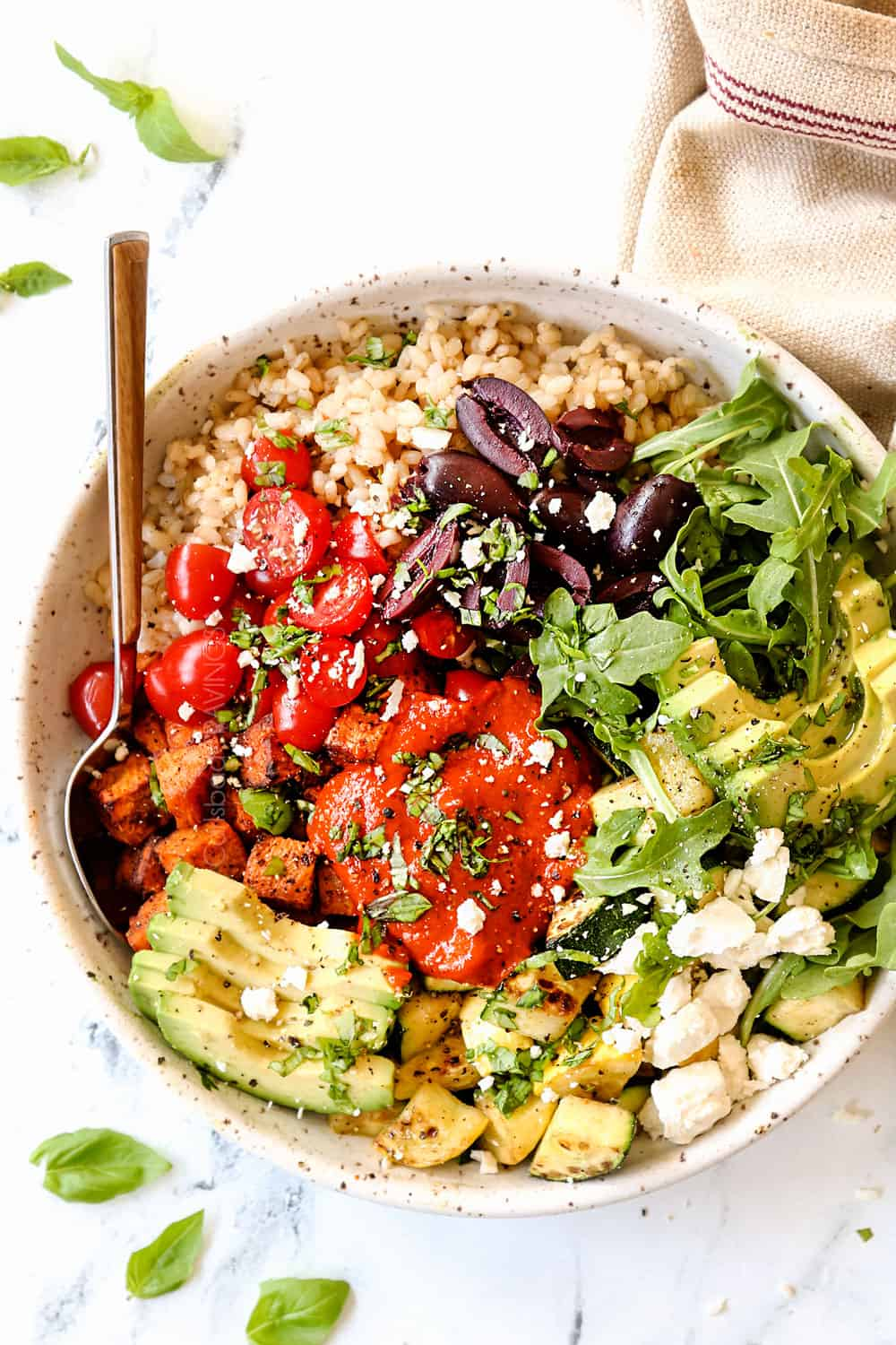 top view showing how to use roasted red pepper sauce by adding it to a Mediterranean bowl