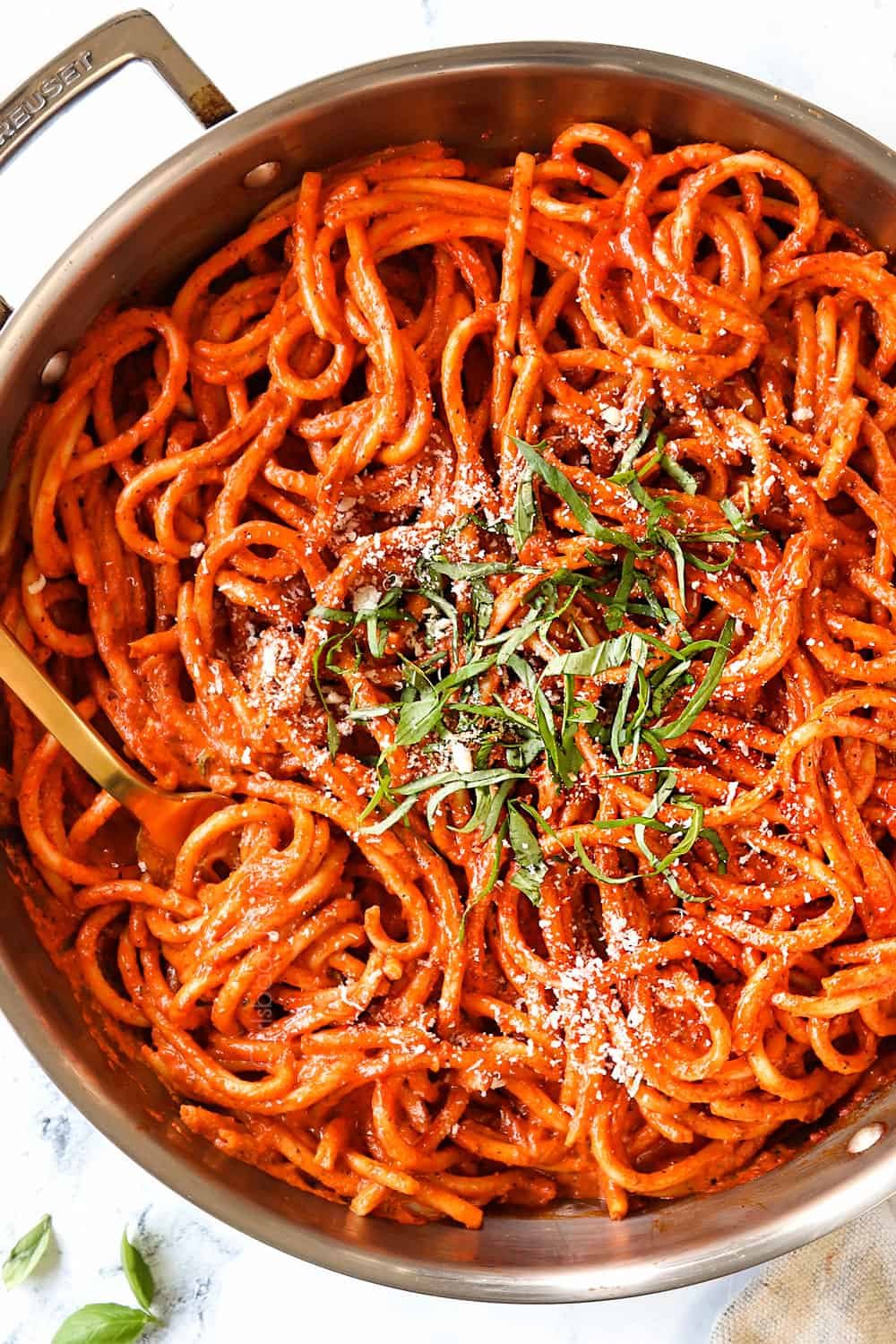 top view of roasted red pepper pasta in a skillet garnished with basil