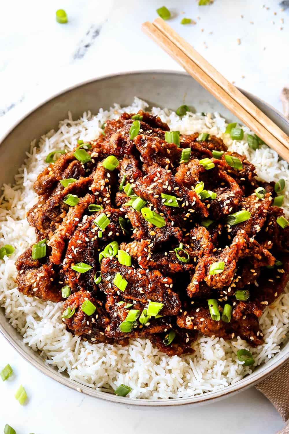 up close of Chinese ginger beef over rice showing how crispy the beef is