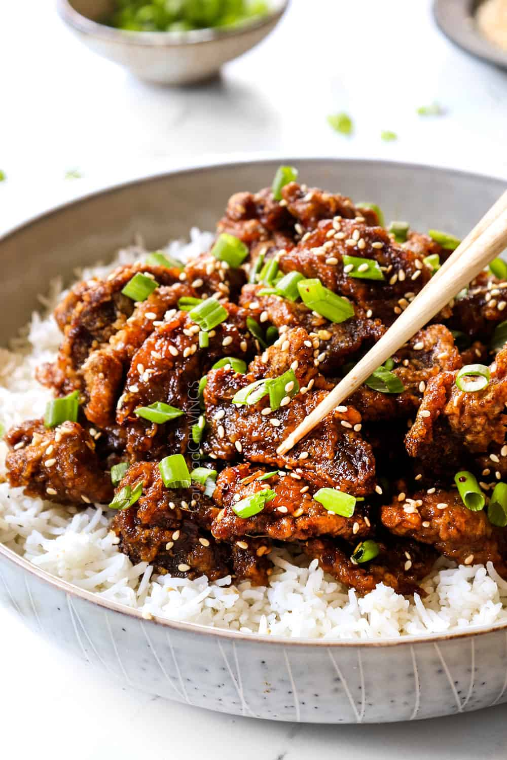 up close of picking up a piece of ginger beef with chopsticks